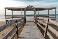 Wooden bridge leading to seaside. Cloudy sky Royalty Free Stock Photography