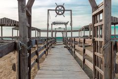 Wooden bridge leading to seaside. Cloudy sky Royalty Free Stock Images
