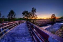 Wooden Bridge Leading to Sunset Landscape Royalty Free Stock Photo