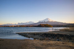 A wooden bridge on the meadow with the lake and Mount Fuji. Stock Photos