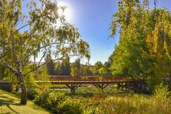 Wooden Bridge on a natural context. Amazing Nature view of a Wooden Bridge on a Sunny Autumn day Stock Photos