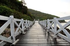 The wooden bridge near to sea with the mountains on the background after rain. Pattaya, Thailand Stock Photography