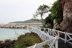 The wooden bridge near to sea with the mountains on the background after rain. Pattaya, Thailand Stock Photo