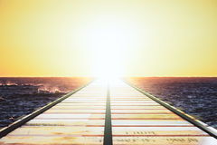 Wooden bridge in the ocean leaving to the horizon at sunset Stock Image