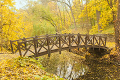 Wooden bridge in old park. Old Wooden bridge across small river in autumn park Royalty Free Stock Photography