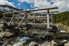 Wooden bridge over alpine lake in Tatra mountains Stock Photo