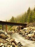 Wooden bridge over Alps rapids on quick mountain river in Alps. Wooden bridge over Alps rapids on quick mountain torrent in Alps, water is flowing over big white Stock Images
