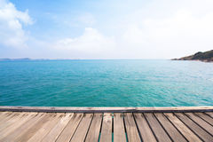 Wooden bridge over blue sea and tropical island beach Royalty Free Stock Image