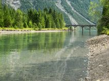 Wooden bridge over canal by the Lake Plansee Royalty Free Stock Image