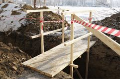 Wooden bridge over dug trench. Royalty Free Stock Images