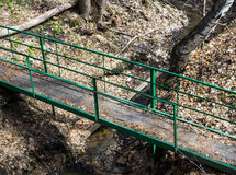 Wooden bridge over a forest stream. Iron railings. View from above. Horizontal photo Royalty Free Stock Image