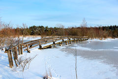 A wooden bridge over a frozen river Stock Image