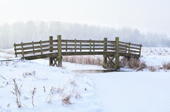 Wooden bridge over frozen river Royalty Free Stock Images