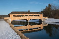 Wooden bridge over isar river, reflecting in the water. On a bright sunny winter day Royalty Free Stock Photo