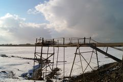 Wooden bridge over the lake in winter. In summer the bridge is almost on the same level with water Royalty Free Stock Photos