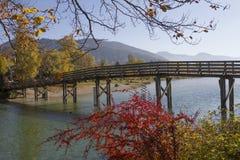 Wooden bridge over mangfall river, effluent stream of lake teger Royalty Free Stock Photo