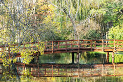 Wooden bridge over mirrored lake in the beautiful autumn park Royalty Free Stock Photo