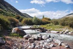 Wooden bridge over a mountain river in Kyrgyzstan. Highlands, mountain river, homemade wooden bridge across the river, bushes and grass Royalty Free Stock Image