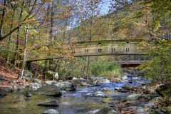 Wooden bridge over mountain stream Stock Image