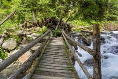 Wooden bridge over mountain stream Stock Photography