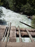Wooden bridge over a mountain stream Stock Images