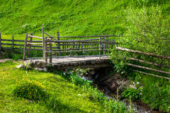 Wooden bridge over narrow stream. Old wooden bridge of planks over narrow stream on hillside with green grass Royalty Free Stock Photos