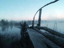 Wooden bridge over the river. Wooden destroyed bridge over the river in the evening mist stock photography