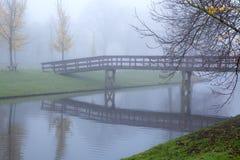 Wooden bridge over river in fog Stock Images