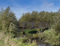 Wooden Bridge Over River. Wooden footbridge across a small river in England stock photography