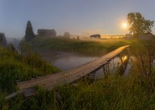 Wooden bridge over the river. Moonlit night in an ancient Russian village royalty free stock photo