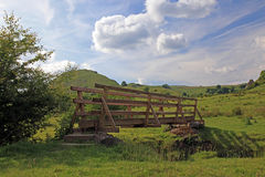 Wooden bridge over a river in the Peak District National Park. Stock Photography