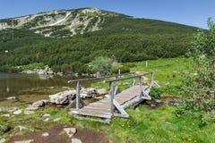 Wooden bridge over river in Pirin Mountain, Bezbog lake and peak Stock Photos