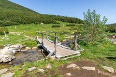 Wooden bridge over river in Pirin Mountain near Bezbog lake Royalty Free Stock Image