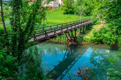 Wooden bridge over the river. Bridge and the reflection of the sky in water Royalty Free Stock Images
