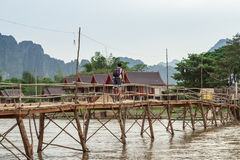 Wooden bridge over river song to riverside guesthouse. Stock Images