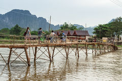 Wooden bridge over river song to riverside guesthouse. Stock Photos