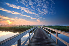 Wooden bridge over river at sunrise Stock Images