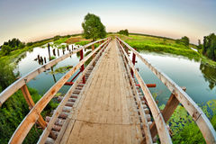 Wooden bridge over the small river Royalty Free Stock Images