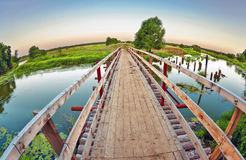 Wooden bridge over the small river Royalty Free Stock Image