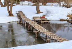 Wooden bridge over a small river. Winter day Royalty Free Stock Photo