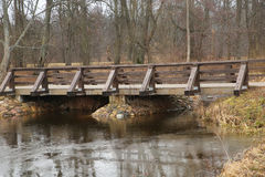 Wooden bridge over a small river. At winter time Royalty Free Stock Images