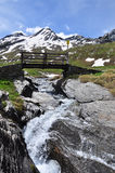 Wooden bridge over a stream. Aosta Valley, Italy Royalty Free Stock Photo