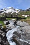 Wooden bridge over a stream. Aosta Valley, Italy Royalty Free Stock Photo