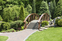 Wooden bridge over the stream, as an element of landscape design Stock Image