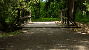 Wooden bridge over the stream in the park. A stand still wooden bridge over the stream connecting two gravel lanes in the park stock image