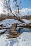 Wooden bridge over a stream. Winter day Royalty Free Stock Photos
