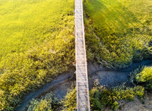 Wooden bridge over a swamp from above. Wooden bridge over a swamp aerial view Royalty Free Stock Images