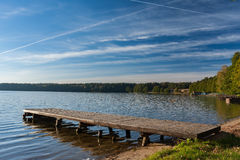 Wooden bridge over a tranquil lake Stock Images