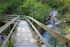 Wooden bridge over waterfall for hikers in the mountains. Wooden brigde in the mountains in Switzerland for hikers. Bridge over a waterfall royalty free stock photo