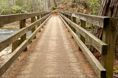 Wooden bridge over a white water stream. Stock Images